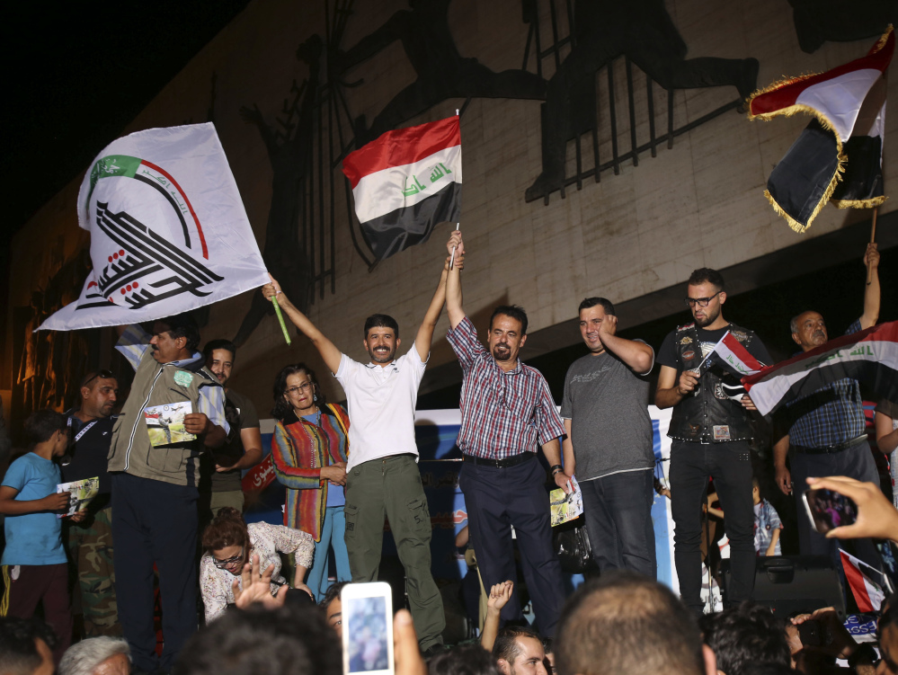 Iraqis wave national flags in Baghdad's Tahrir square on Monday, celebrating news of the army's victory in Mosul after nearly nine months of grueling urban combat against Islamic State extremists. Coalition airstrikes earlier Monday pounded the last ISIS-held territory.