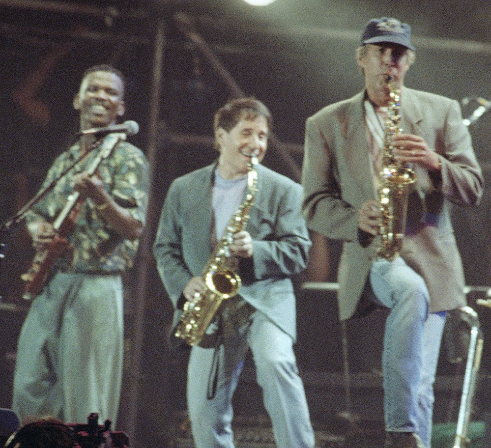 Paul Simon, center, plays a finale with lead guitarist Ray Phiri, left, and actor-comedian Chevy Chase in New York's Central Park in 1991.