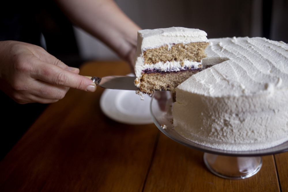Christine Burns Rudalevige takes a piece of an old-fashioned spice cake with blueberry jam and whipped cream frosting.