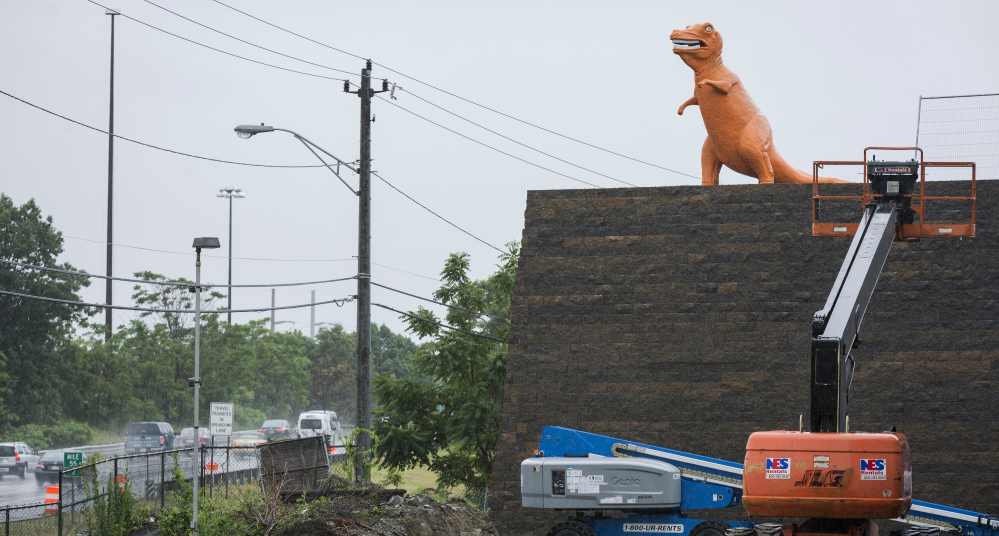 An orange dinosaur statue, a fixture on Route 1 in Saugus, Mass., for years, looks down from its new perch. The site it sits on was sold, but popular demand kept the dino from extinction.