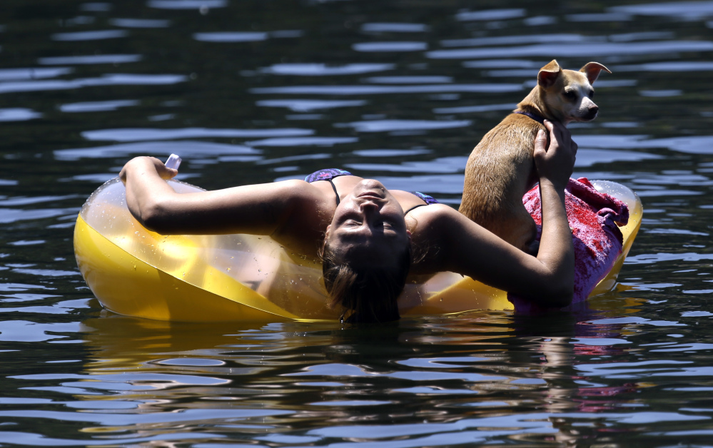 Justine Hicks floats with her dog, Kiana, on the Willamette River in Portland, Ore., in July 2015. The river once shunned by swimmers is enjoying a renaissance now that it's been cleaned up. The city is partnering with a civic group this summer to entice residents into the water.