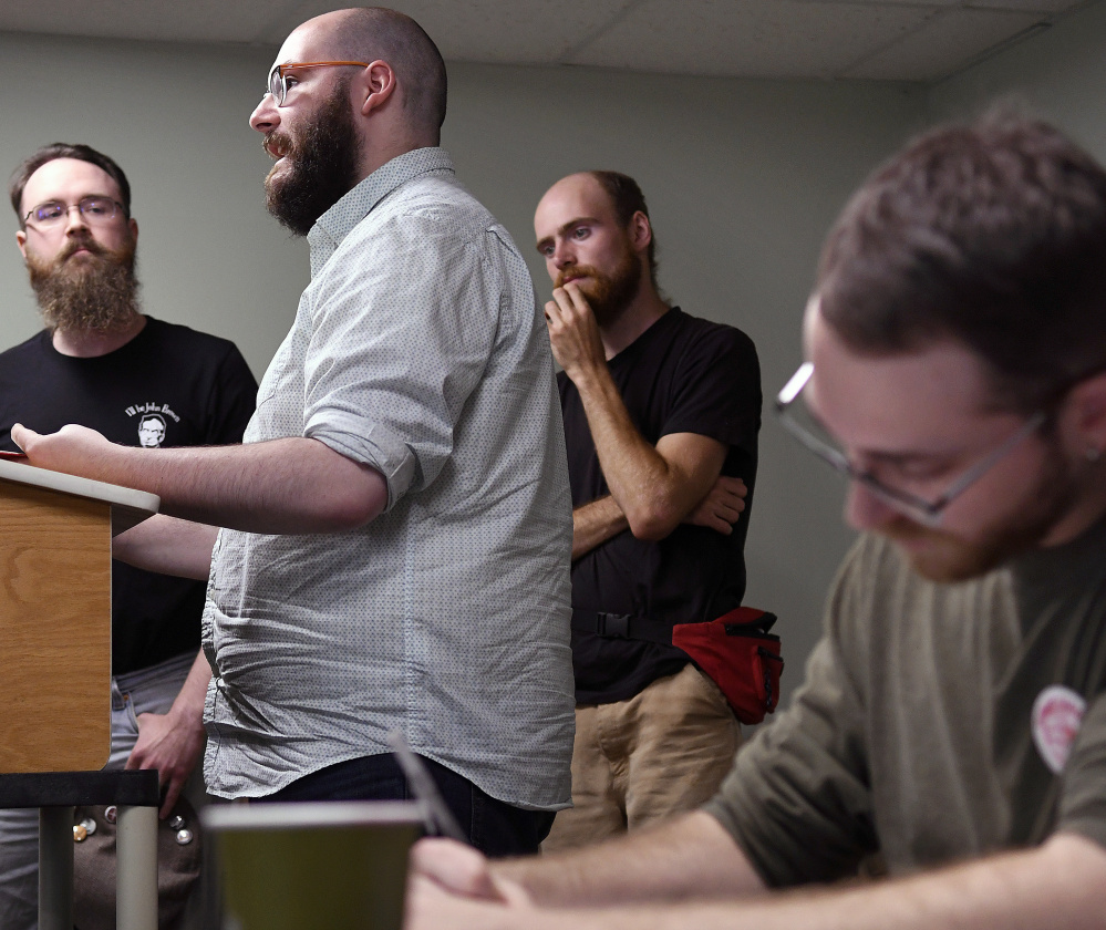 Jeremy Claywell, right, takes notes Sunday during a presentation by members of the Maine John Brown Gun Club during a meeting of the budding Socialist Party of Maine in Augusta.