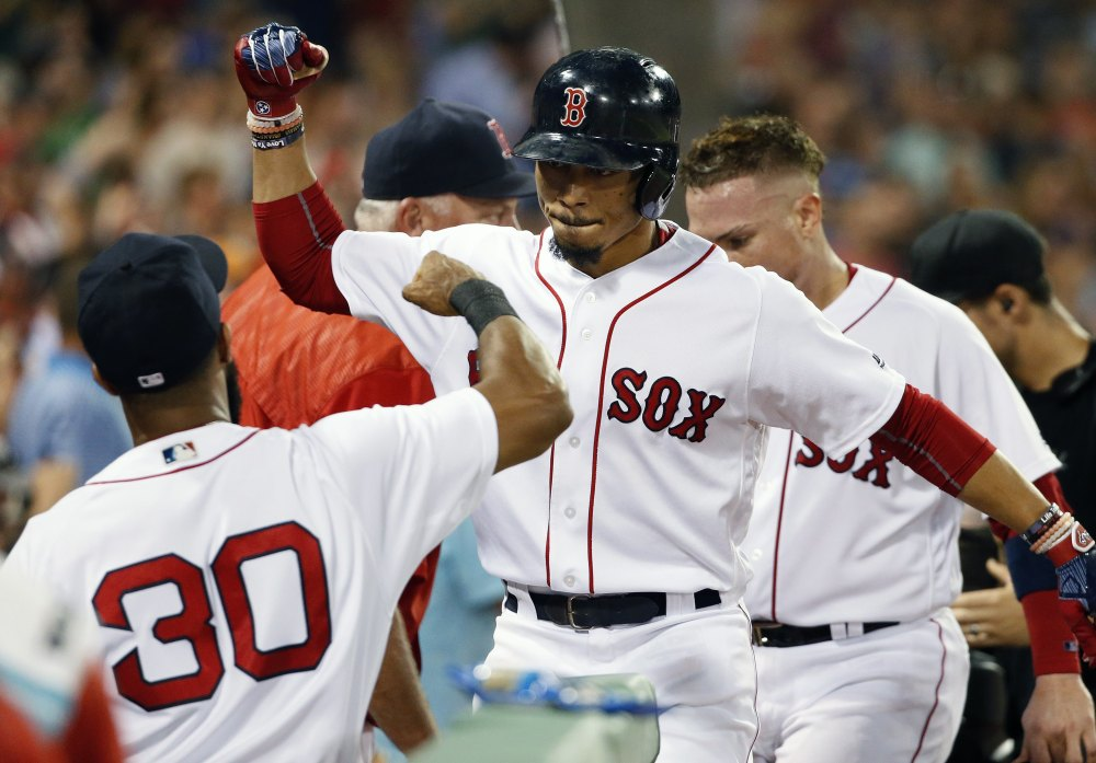 Mookie Betts, center, celebrates with Chris Young after hitting a two-run homer in the third inning Sunday night against the New York Yankees, ending a 24-inning scoreless streak for the Red Sox. Boston won, 3-0, to earn a split of the four-game series after losing 3-0 in the opener of the day-night doubleheader. Story, C5