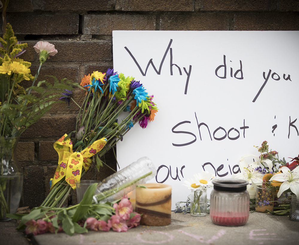 A makeshift memorial at the scene where a Minneapolis police officer shot and killed Justine Damond, a yoga and meditation instructor, included this handwritten sign Monday.