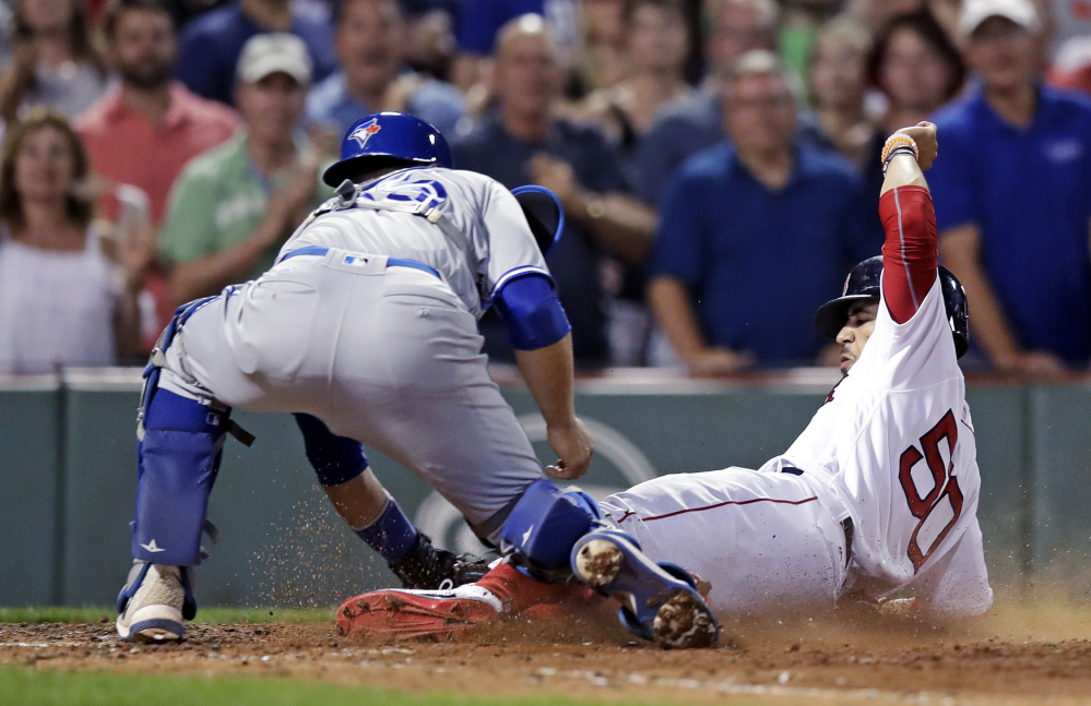 Toronto catcher Russell Martin tags out Mookie Betts, who was trying to score the go-ahead run on a single by Dustin Pedroia in the seventh inning Monday night at Fenway Park. Toronto went ahead in the next inning and held on for a 4-3 win.