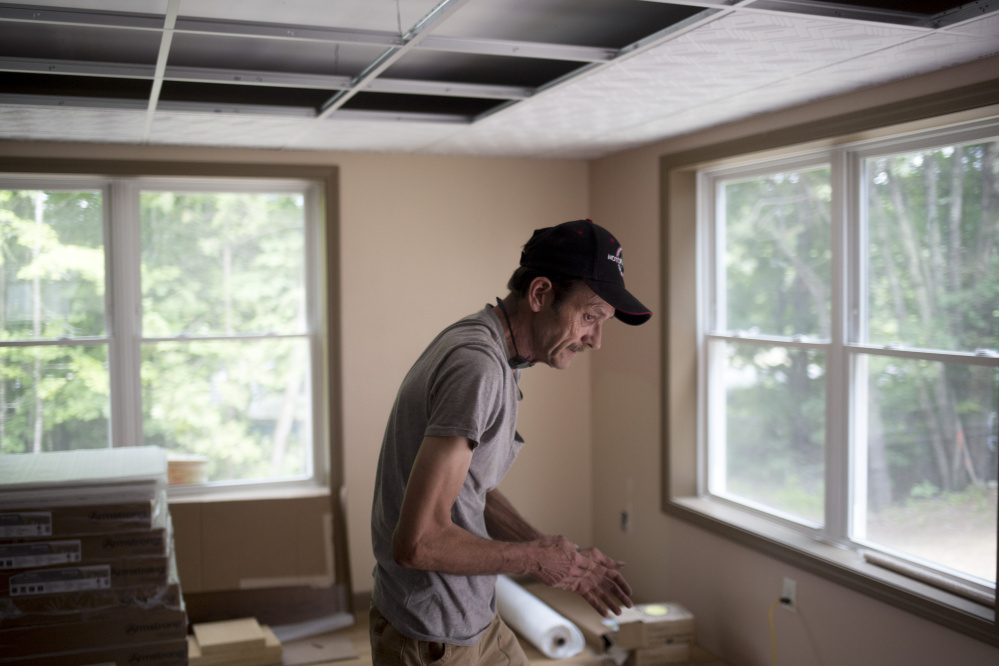 Joe St. Pierre walks through the living room of his new home in Chesterville after a day of helping volunteers work on putting the finishing touches on it.
