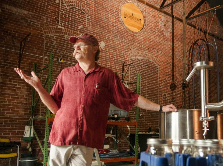 Standing beside the still, master distiller Dan Davis talks about the rum-making process Thursday during a tour of Sebago Lake Distillery.