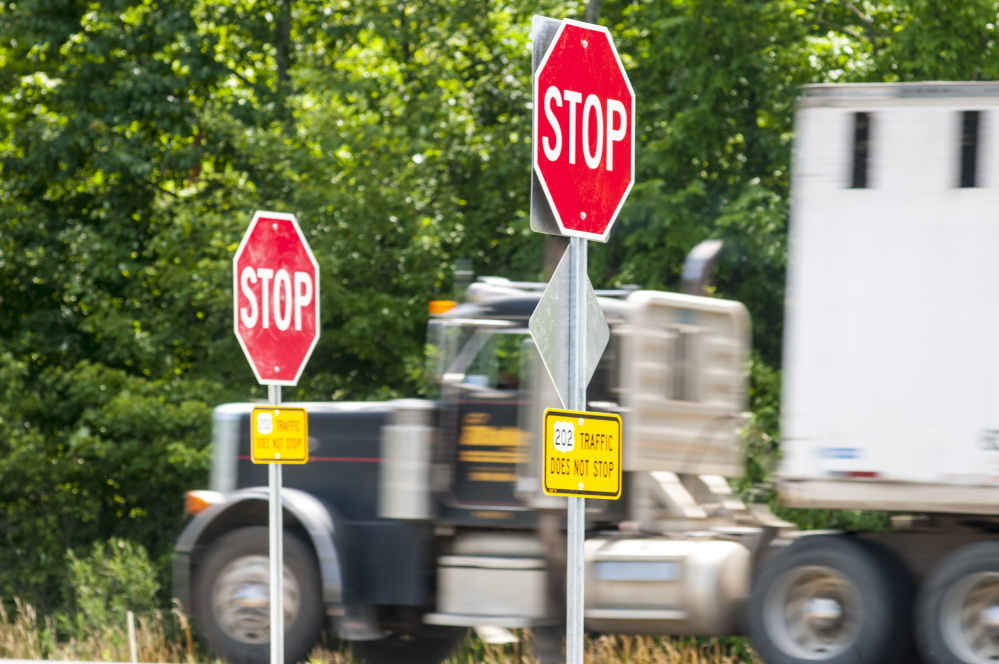 A tractor-trailer on U.S. Route 202 zooms past stop signs at Main Street intersection on Friday in Winthrop.