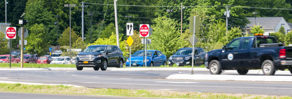 A line-up of cars, left, waits to turn left off Main Street and onto U.S. Route 202 on Friday in Winthrop. The turning traffic has stop signs, but the highway traffic does not.