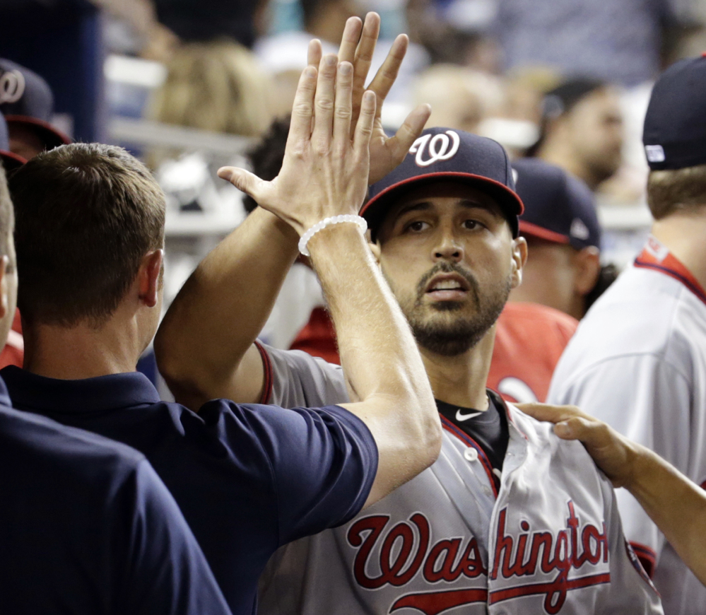 Nationals pitcher Gio Gonzalez is high-fived in the dugout after being relieved during the ninth inning against the Miami Marlins on Monday in Miami. Gonzalez gave up a single to Dee Gordon in the ninth inning to end his bid for a no-hitter.