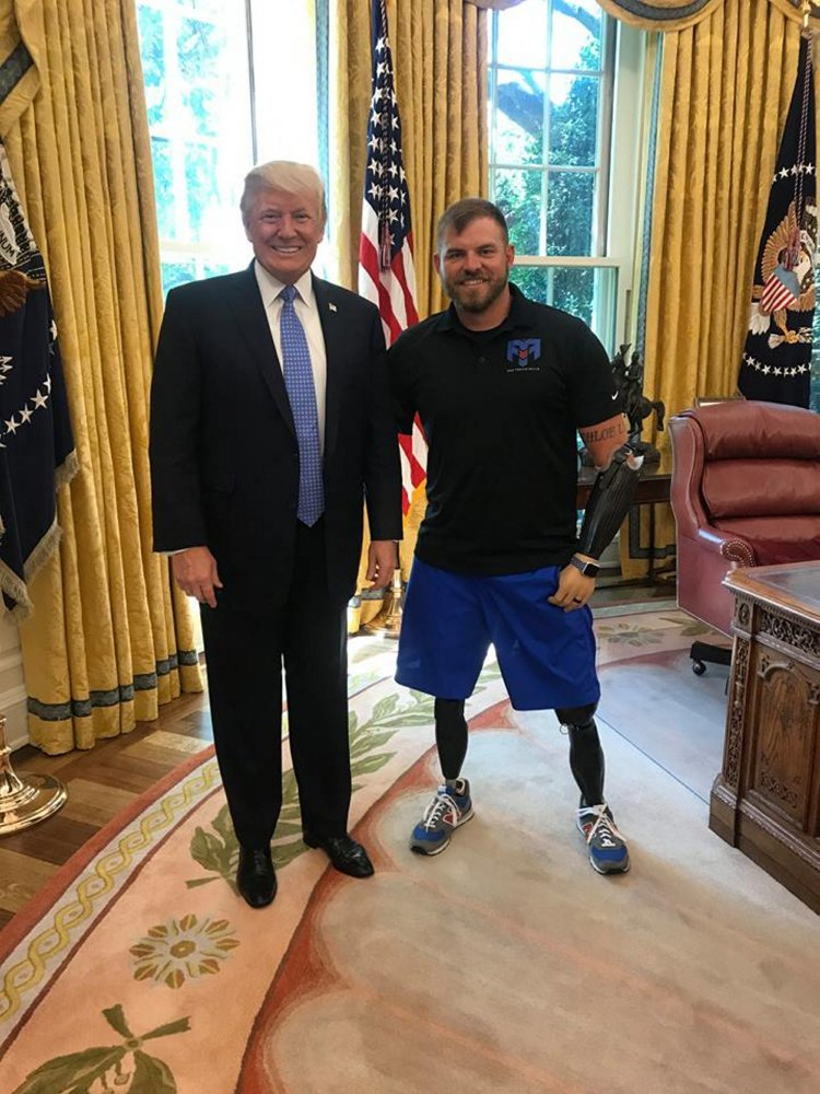 Staff Sgt. Travis Mills, right, poses with President Donald Trump on Monday during a trip to meet with Vice President Mike Pence to discuss veterans' issues.
