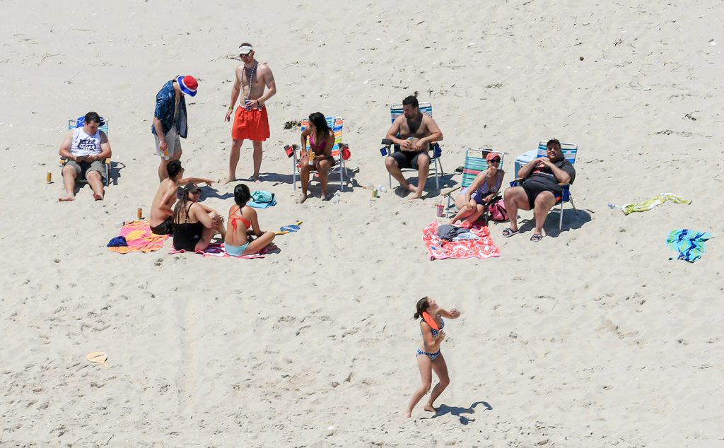 New Jersey Gov. Chris Christie, right, uses the beach with his family and friends at the governor's summer house at Island Beach State Park in New Jersey on Sunday. Christie is defending his use of the beach, closed to the public during New Jersey's government shutdown, saying he had previously announced his vacation plans and the media had simply
