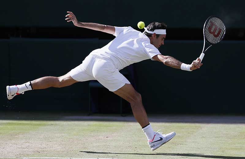 Roger Federer returns to  Tomas Berdych during their Men's Singles semifinal match on Friday,