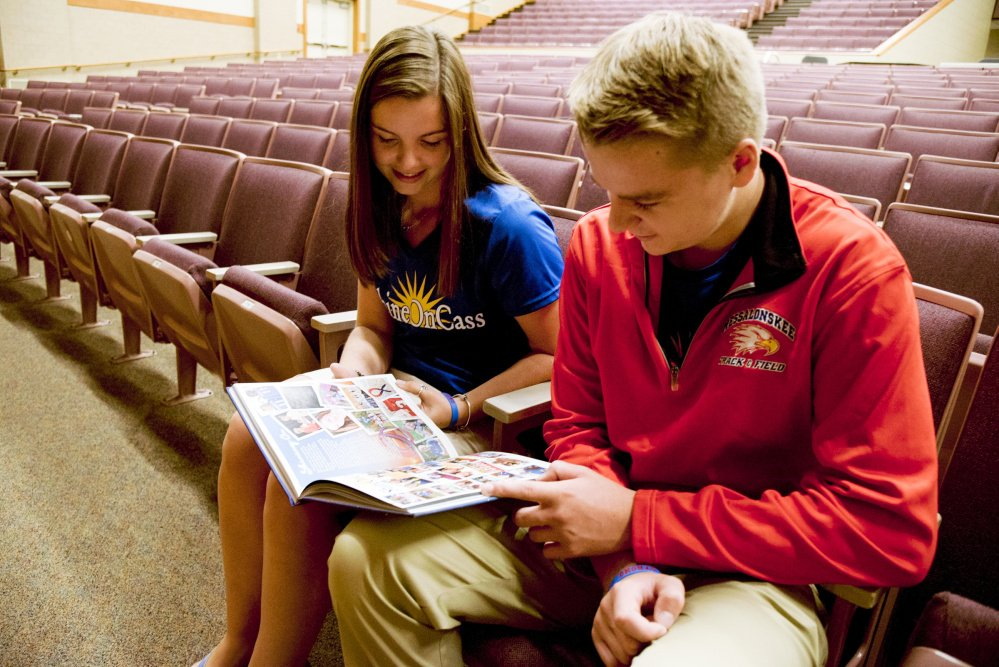 Shawna Oliver, a friend of Cassidy Charette and a member of the ShineOnCass Foundation board, and Charette's brother, Colby, look at a tribute to Cassidy in the Messalonskee High School yearbook on Wednesday at the high school.