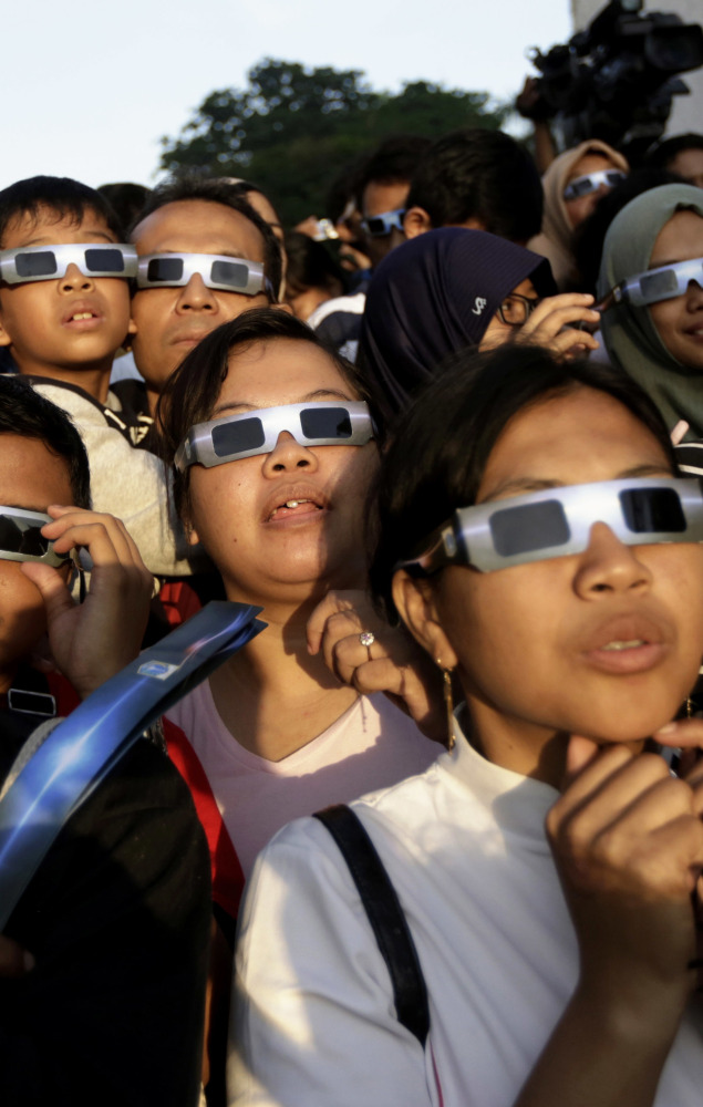 People wearing protective glasses look up at the sun to watch a solar eclipse in Jakarta, Indonesia, in 2016.
