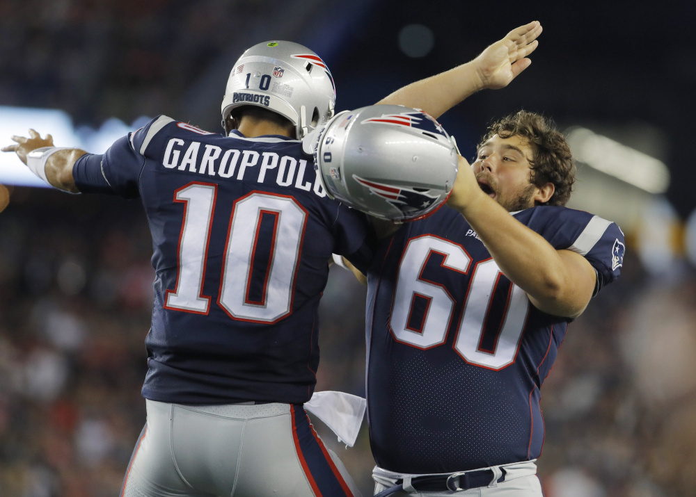Patriots center David Andrews (60) celebrates with quarterback Jimmy Garoppolo after a New England touchdown against the Jacksonville Jaguars in the second quarter Thursday night at Gillette Stadium. Jacksonville held on for a 31-24 win in both teams' preseason opener.