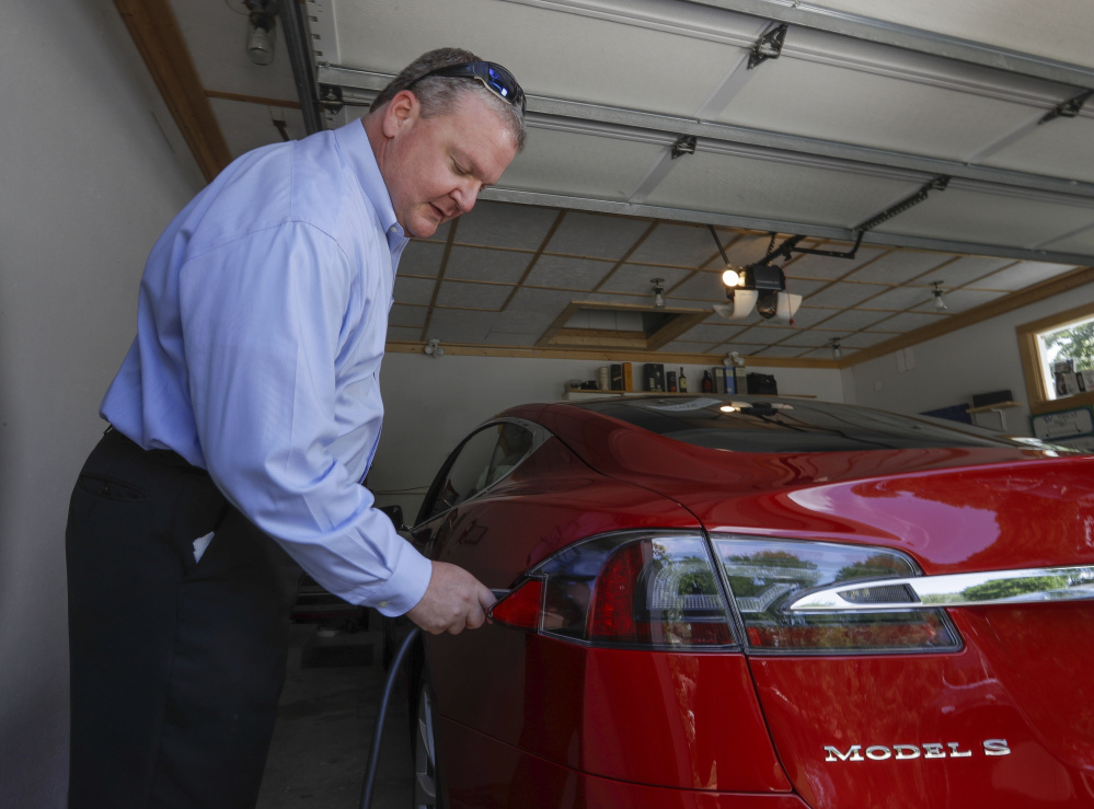 Jeff Solie charges his electric Tesla sedan at his home in New Berlin, Wis., last month. Electric cars are seeing growing support around the world. But there's a problem: There aren't enough places to plug in. Solie says his home system allows him to rely on electric as his primary mode of travel.