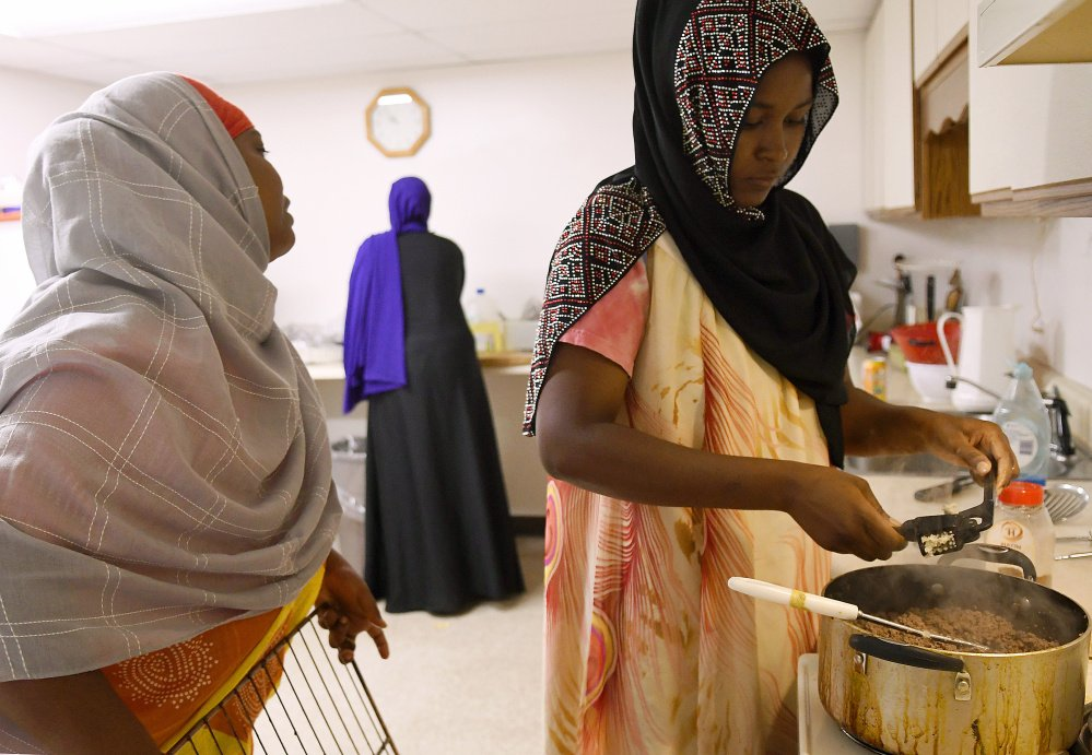 Women prep deep-fried sambusas at the Viles Arboretum kitchen in Augusta for the Beyond Borders Farmers Market. Khadija Hussein, left, Asli Hassan and Farhiya Ibrahim serve the traditional Somali food at the market run by refugees who have resettled in Maine.