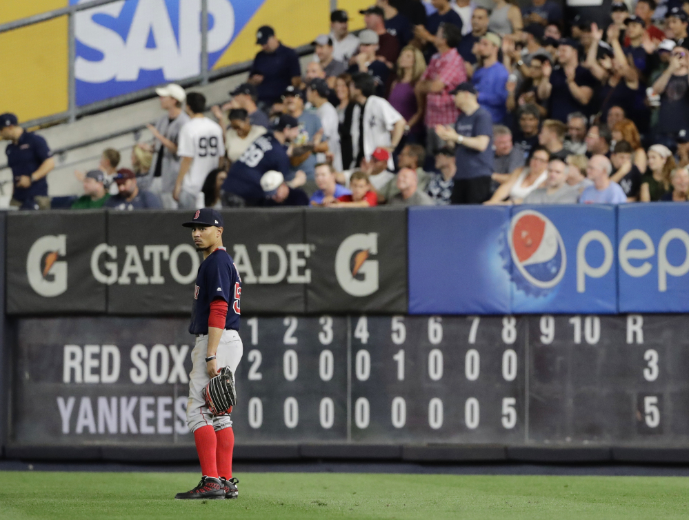 The scoreboard shows the damage as Mookie Betts stands in the outfield in the decisive eighth inning.