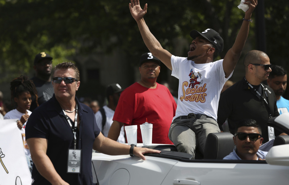 Grammy Award-winning artist Chance the Rapper, center, the grand marshal of the 2017 Bud Billiken Parade, waves at the crowds during Saturday's festivities in Chicago.