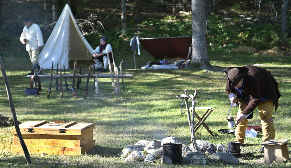 Ben Pierce of Vassalboro scoops coffee from a fire pit Sunday during the re-enactment held at the Pownalborough Court House in Dresden. The re-enactors portrayed militia members during the French and Indian War of 1755.