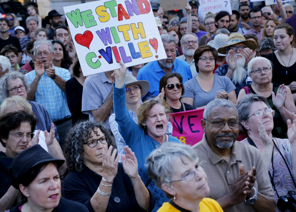 People cheer while listening to a speaker at an event Aug. 13 in Monument Square called