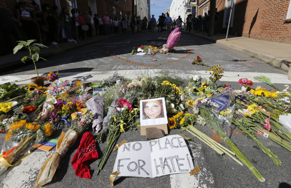 A makeshift memorial of flowers and a photo of victim Heather Heyer sits in Charlottesville, Va., on Sunday. Heyer died when a car rammed into a group of people protesting the presence of white supremacists who had gathered in the city for a rally Saturday.