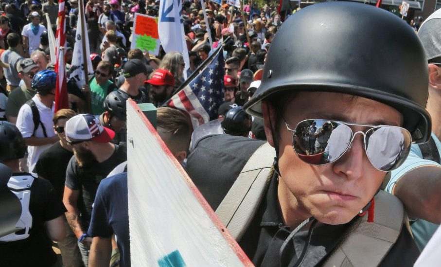 A white nationalist demonstrator with a helmet and shield walks into Lee Park in Charlottesville, Va., on Saturday. Hundreds of people chanted, threw punches and unleashed chemical sprays on each other.