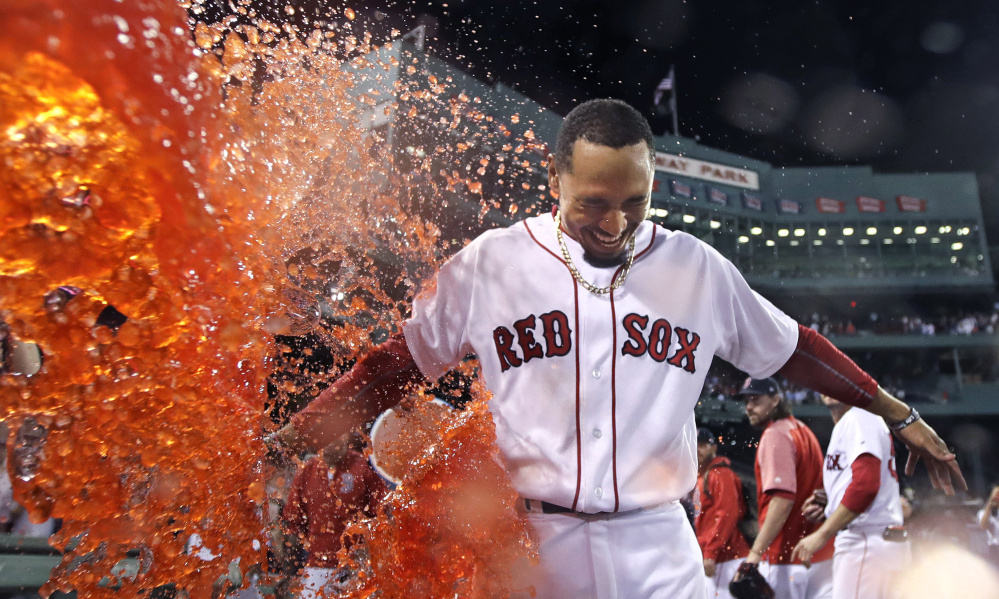 Mookie Betts is doused after his walk-off two-run double in the ninth inning Wednesday night against the St. Louis Cardinals at Fenway Park. Betts' two-out double gave Boston a 5-4 win.