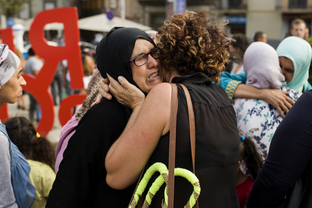 Families of young men believed responsible for the attacks in Barcelona and Cambrils gather along with members of the local Muslim community to denounce terrorism in Ripoll, Spain, on Saturday.