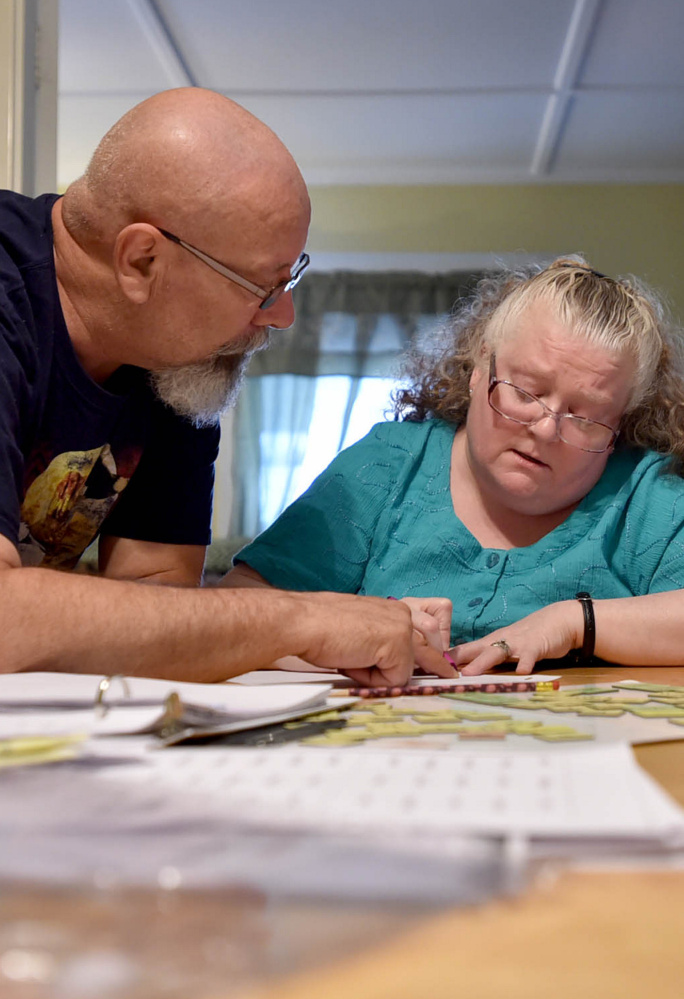 Howard Gagnon helps his wife, Mona, with a reading lesson at the family's home on Gilman Street in Waterville in July.