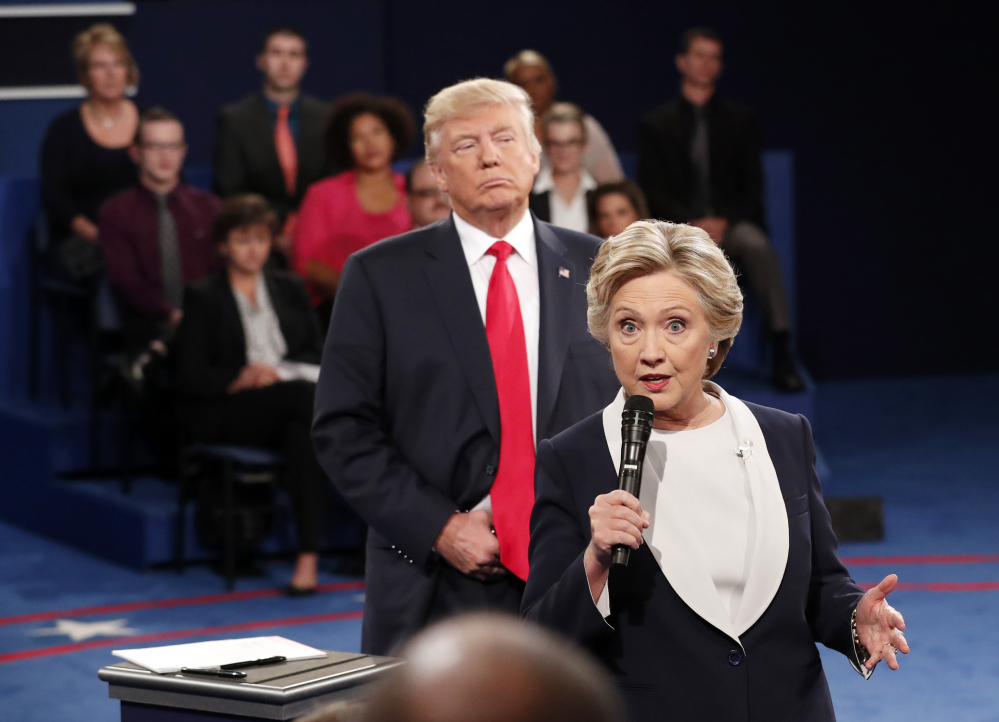 During a moment in the Oct. 9, 2016, debate, Democratic presidential nominee Hillary Clinton speaks as Republican presidential nominee Donald Trump stands behind her.