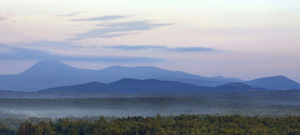 Early morning haze colors Mount Katahdin and its surrounding mountains, seen from land along Route 11 in Patten. The viewpoint is part of the Katahdin Woods and Waters scenic byway.