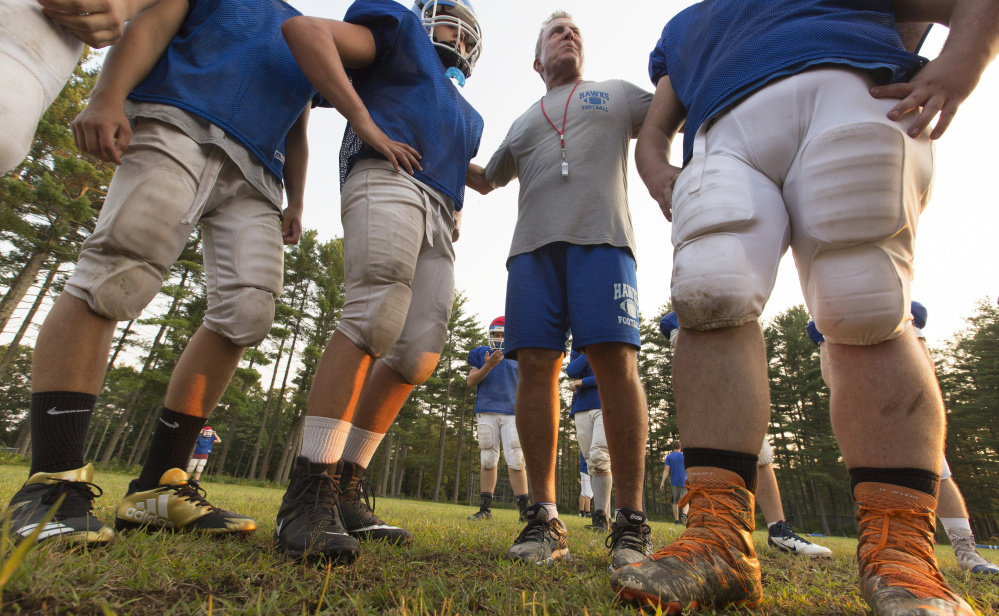 Jim Walsh, head coach for the Sacopee Valley High football team, huddles with players before a drill. Sacopee Valley is returning to varsity status as a member of the new Class E developmental division.