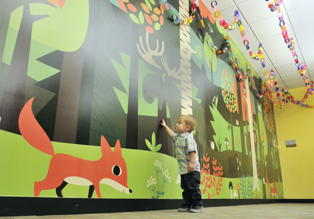 Weston Dube, 19 months old, points to a moose on the children's area wall at Lithgow Public Library in Augusta. There are nearly 3,000 paper rings hanging from the ceiling, each representing an hour of reading in the summer program.