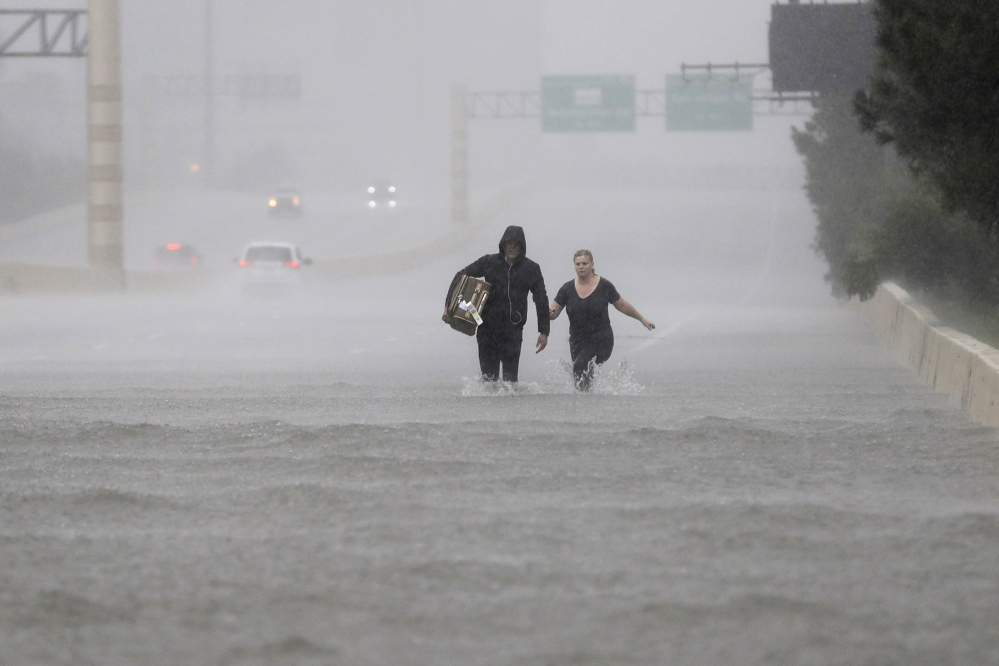 Two people walk down a flooded section of Interstate 610.