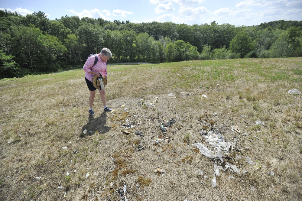 Kim Rich looks at what she thinks may be trash protruding from the closed landfill, which at one time was capped with 2 feet of material. Rich and other residents have pressured the city to deal with issues at the site.