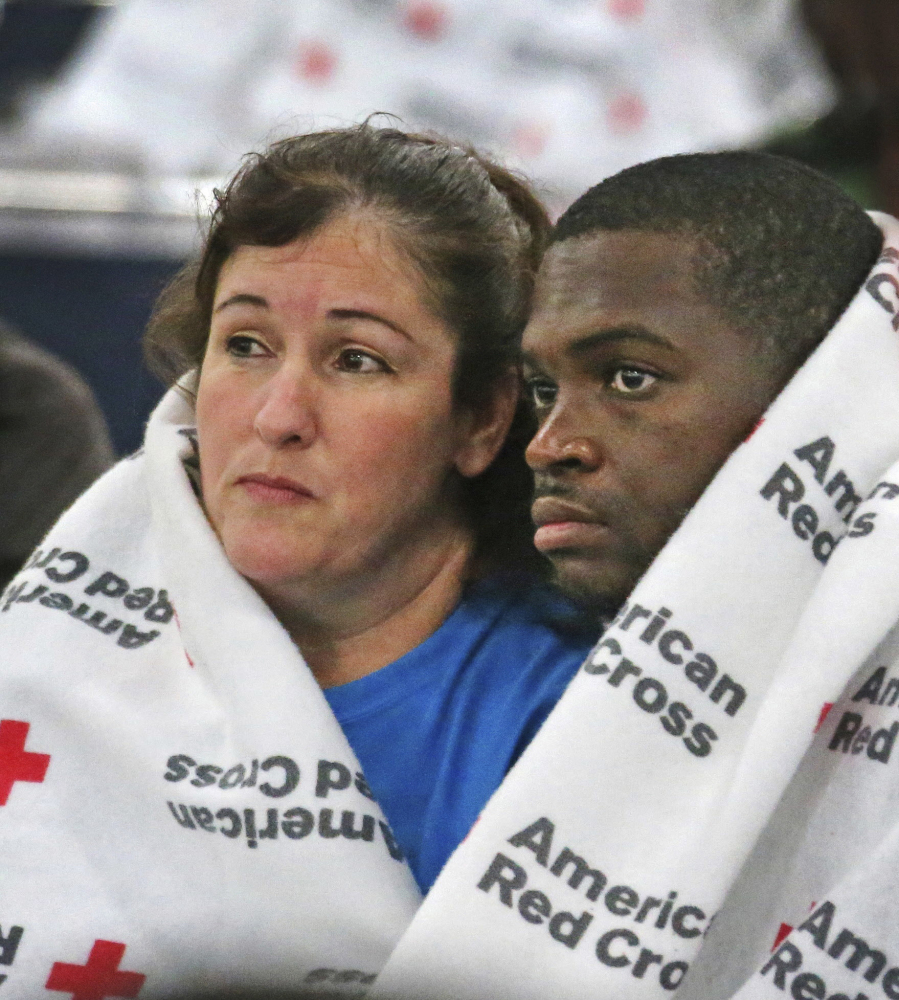 Displaced South Houston residents Oralia Guerra and Diamond Robinson huddle together to stay warm underneath Red Cross blankets at the George Brown Convention Center in Houston on Monday, Aug. 28, 2017, in the wake of Tropical Storm Harvey. Floodwaters reached the rooflines of single-story homes Monday and people could be heard pleading for help from inside as Harvey poured rain on the Houston area for a fourth consecutive day after a chaotic weekend of rising water and rescues.