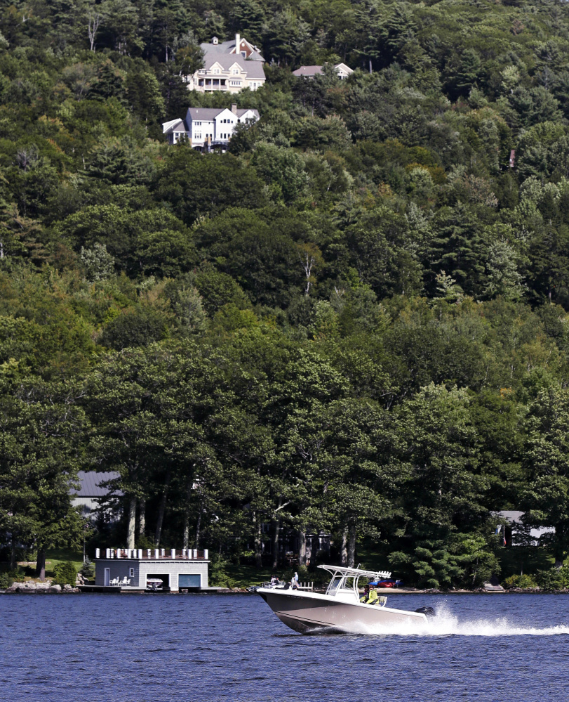 A power boat passes homes built on a hill over looking Lake Sunapee in Newbury, N.H.  Lake residents say it is unfair to suggest they are against access to poor outsiders.