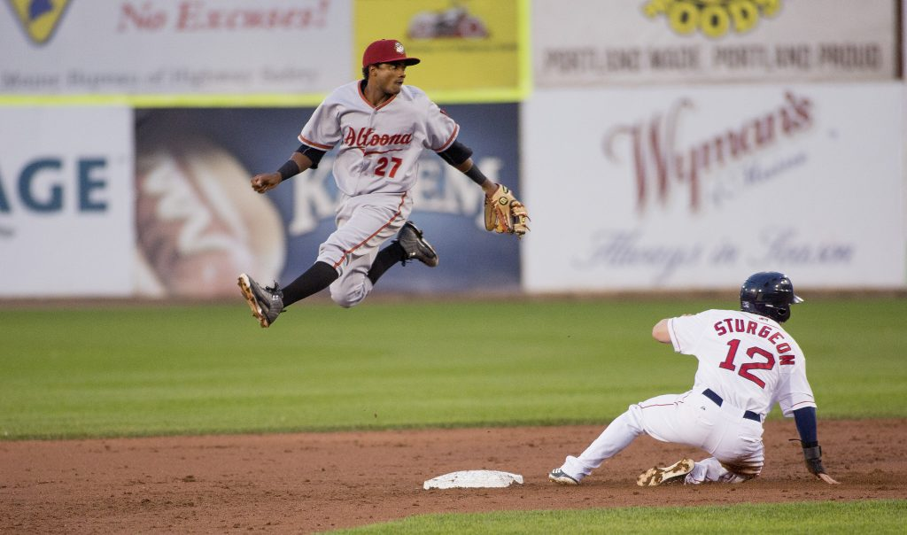 Altoona's Pablo Reyes jumps up in the air as he throws the ball to first as Cole Sturgeon of the Sea Dogs slides into second in Tuesday night's game at Hadlock Field. The Curve beat the Sea Dogs, 5-3.
