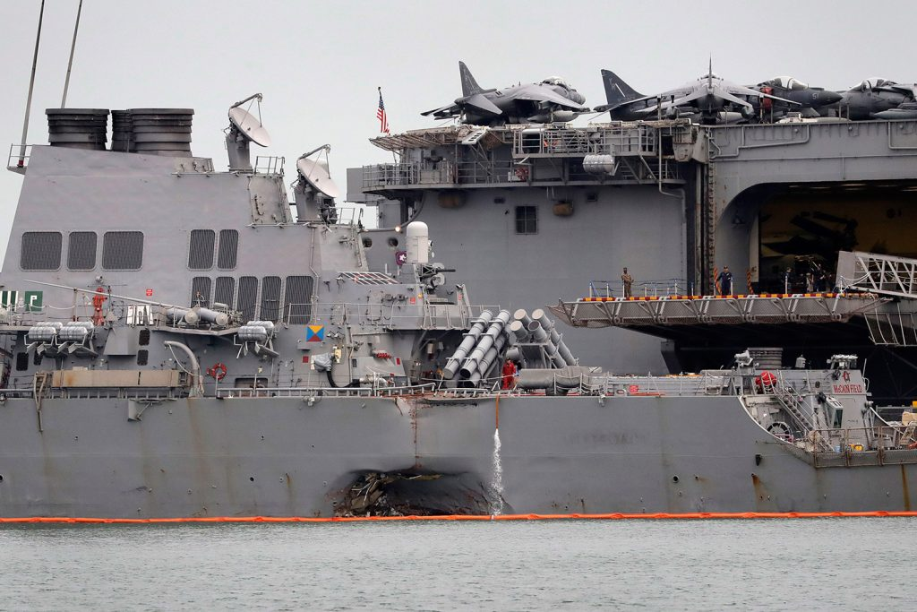 The damaged hull of the USS John S. Mc Cain is seen at Singapore's Changi naval base on Tuesday. Experts say the destroyer's collision with a tanker ship early Monday was likely caused by human error