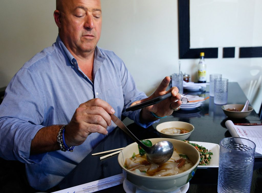 A Maine spice company is developing seven special spice blends for food TV personality Andrew Zimmern's online store, all based on Zimmern's recent travels. He is shown here in July taking a photo of his Taiwanese noodle soup.