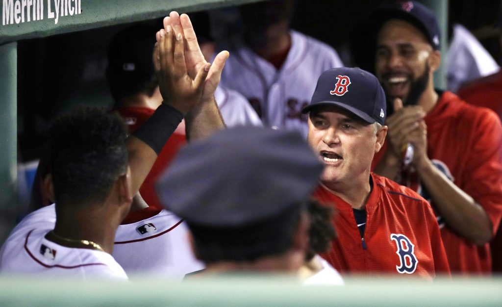 Manager John Farrell congratulates third baseman Rafael Devers, whose alert defense started a triple play Tuesday night for the Boston Red Sox against the St. Louis Cardinals.