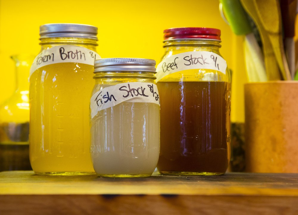Broth stocks are in labeled jars on the kitchen counter.