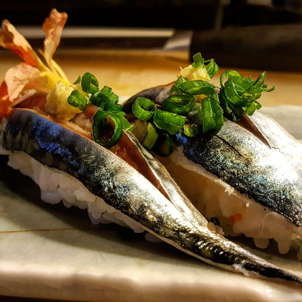 Two pieces of mackerel nigiri topped with ground ginger and scallions.
