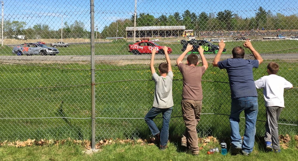 Fans stand against the pit area fencing to watch a race back in May at Unity Raceway in Unity.