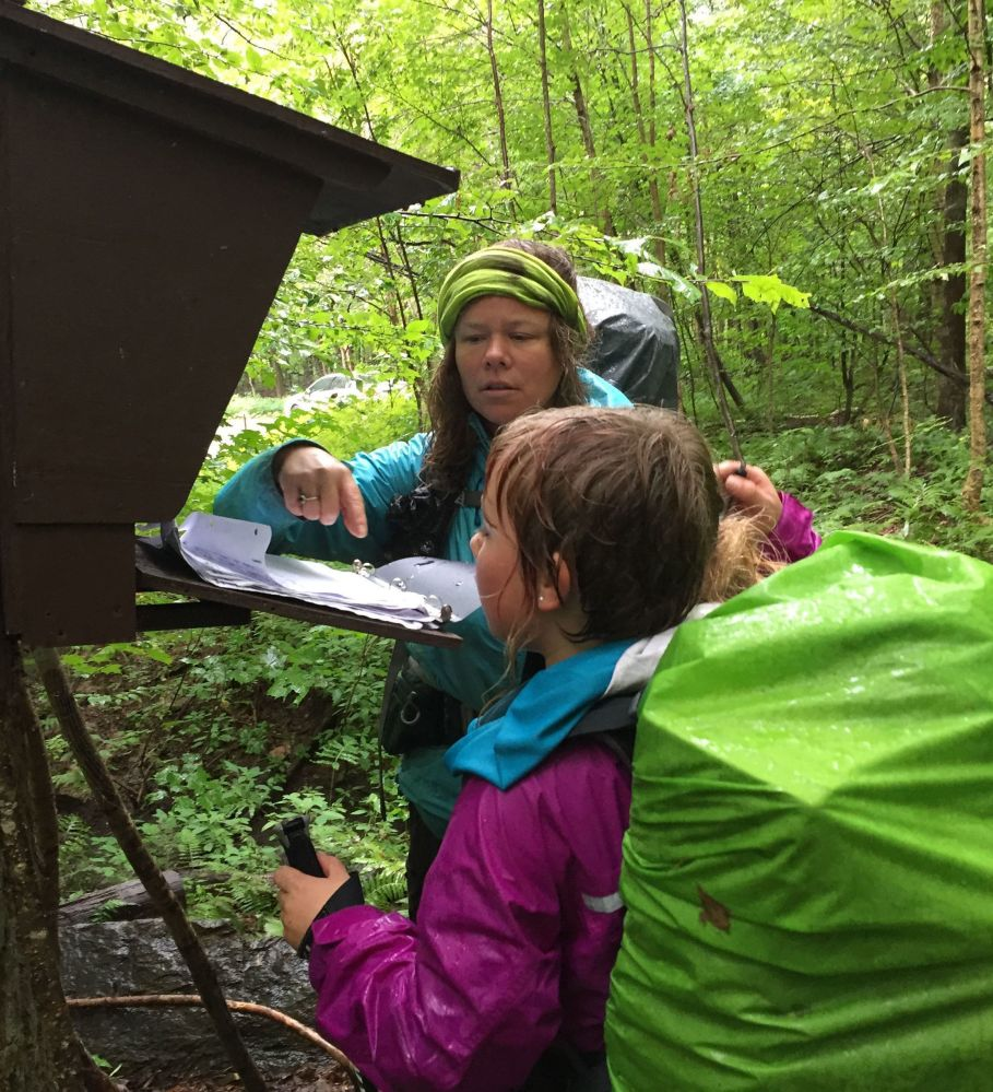 Yarrow Upton and her daughter, Zella, 9, sign a trail register Sunday at the close of their thru-hike of the Long Trail in Vermont, the oldest long-distance trail in the United States.