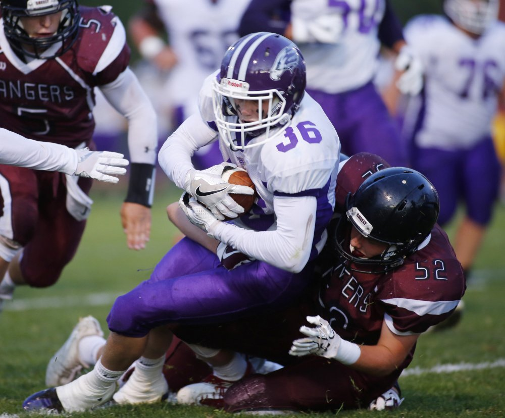 Kyle Glidden of Marshwood High is tackled by Jackson Williams of Greely in the first half of their game Friday night in Cumberland. Marshwood won, 47-14.