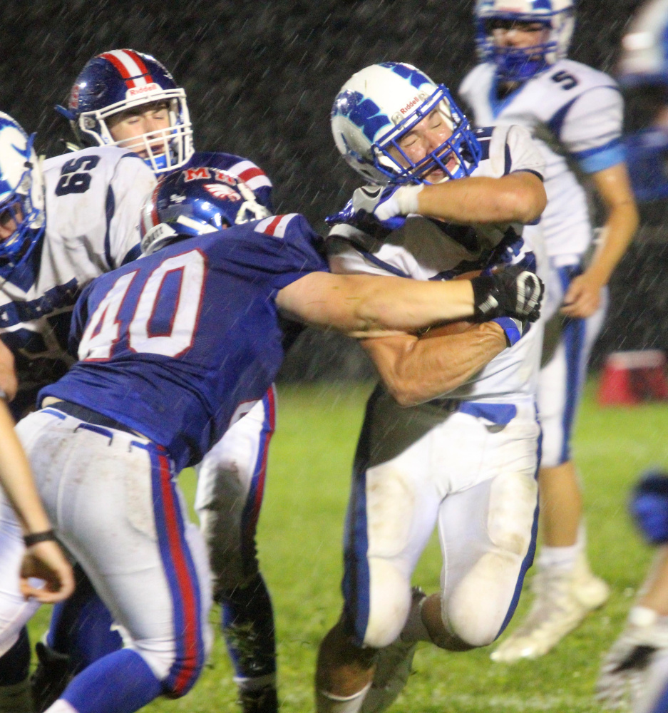 Messalonskee defender Colton Chavarie tries to strip the ball from Kennebunk's Jake Littlefield during the first half of their Class B game Friday night in Oakland. Kennebunk won, 32-7.