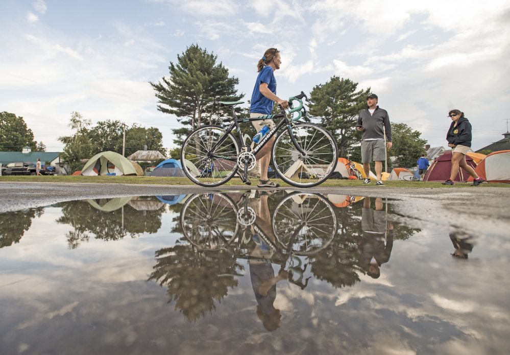 Lynn Jennings of Weld walks her bicycle to her tent Saturday at the Skowhegan Fairgrounds, a day before the start of the fifth annual BikeMaine trek around Maine.